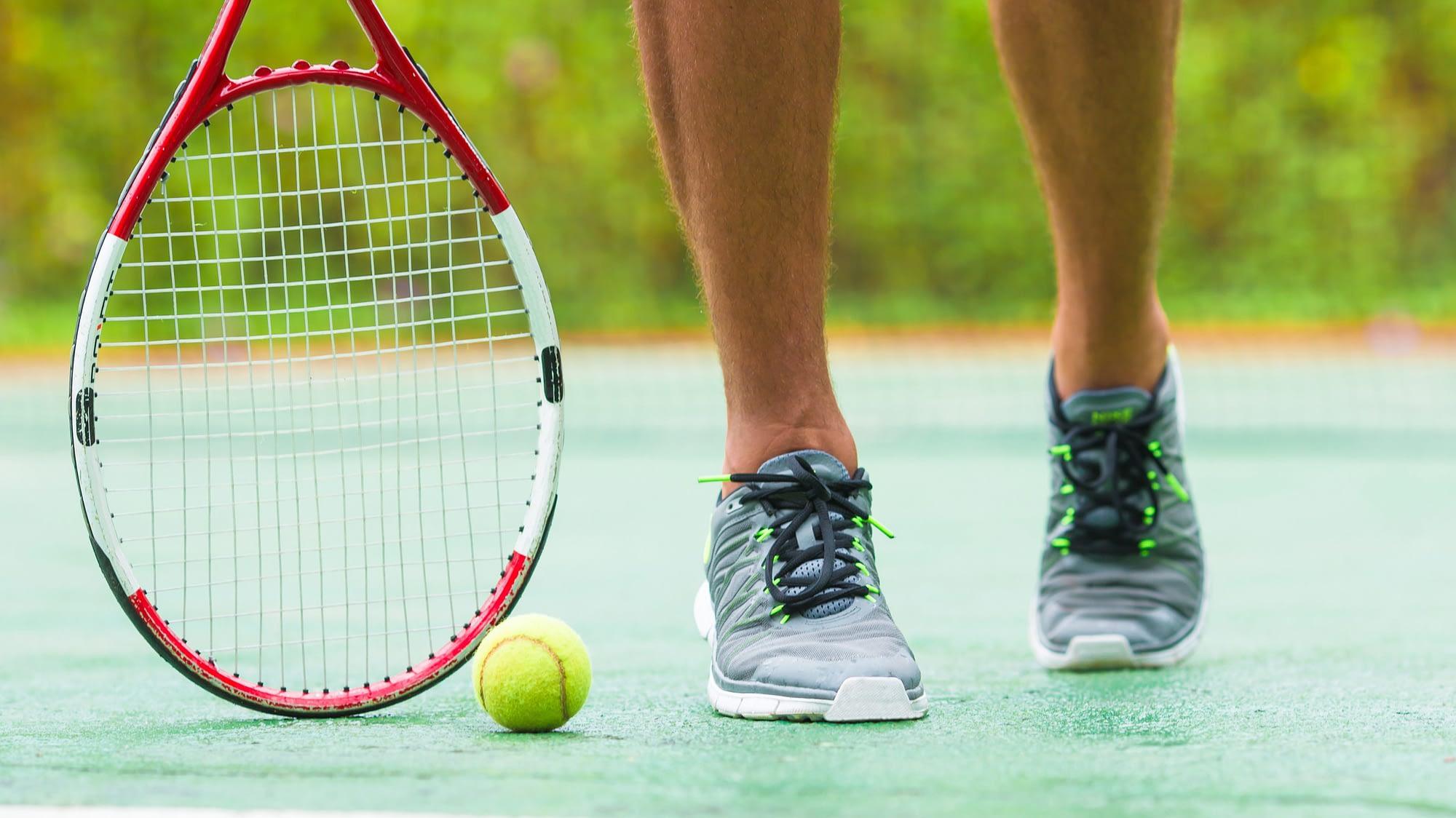 Jambe, raquette et tennis d'un joueur de tennis